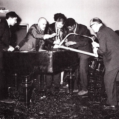 George Maciunas, Dick Higgins, Wolf Vostell, Benjamin Patterson & Emmett Williams performing Philip Corner's Piano Activities at Fluxus Internationale Festspiele Neuester Musik, Weisbaden 1962. Photograph by Hartmut Rekort